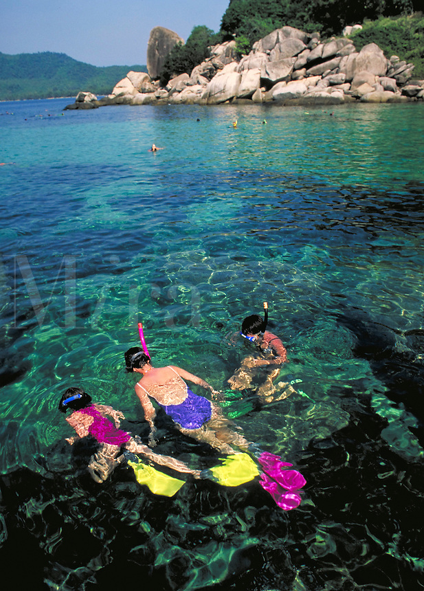 A brightly clothed family snorkels in clear aqua water on a sunny day in Thailand. Ko Samui, Thailand.