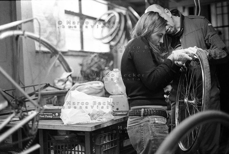 """Milano, quartiere Isola. La Ciclofficina Stecca Associazione +bc. Una ragazza, aiutata dal meccanico, rimuove il copertone dal cerchione --- Milan, Isola district. """"Stecca"""" bicycle cooperative at the +bc association. A girl, aided by the  mechanic, removes the tire from the rim"""