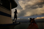 Scot Janikula looks at the clouds as they start to change color during the sunset while his dog Renegade watches from a skiff below.