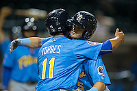 Ian Happ (right) gets a hug from teammate Gleyber Torres (11) after hitting his second home run of the game against the Winston-Salem Dash at BB&T Ballpark on April 18, 2016 in Winston-Salem, North Carolina.  The Pelicans defeated the Dash 6-4.  (Brian Westerholt/Four Seam Images)
