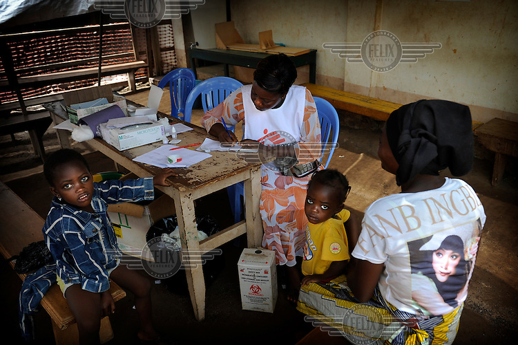 A member of an innoculation team takes details from a mother with two children at Duekoue's hospital.