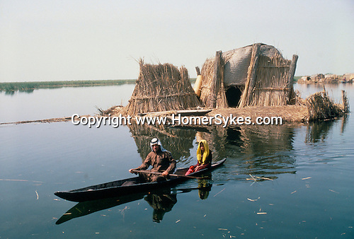 Marsh Arabs. Southern Iraq. Circa 1985. Marsh Arab man with daughter in boats with traditional reed built island home called a kibasha. Haur al Mamar or Haur al-Hamar marsh collectively known now as Hammar marshes Irag 1984