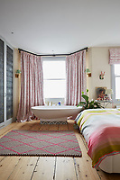 The spacious master bedroom has a free-standing bath in front of the window. The windows are dressed with pink pattern curtains and roman blinds, which coordinate with a green and pink stripe cover on the bed.
