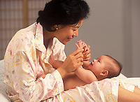 Asian American mother embraces her baby.