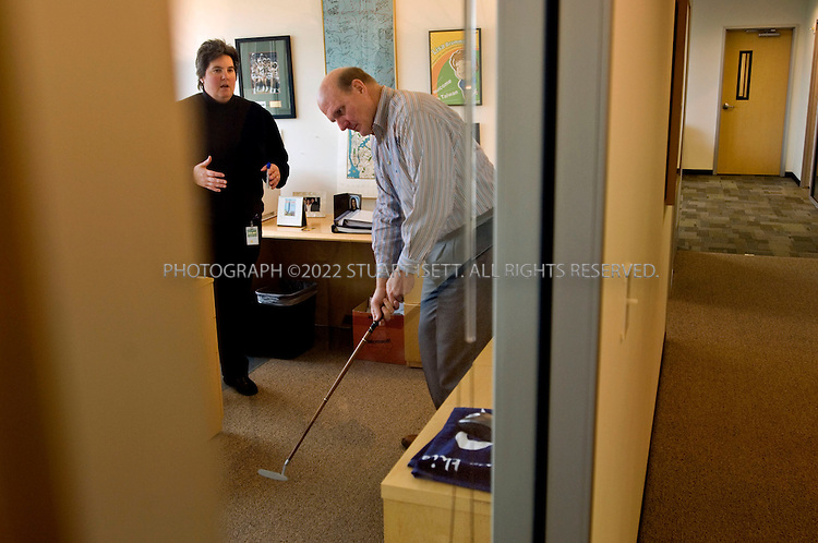 1/23/2006--Redmond, WA, USA..12:10pm: Steve Ballmer, CEO of Microsoft, putts golf balls during a meeting with Lisa Brummel, Senior Vice President of Human Resources, in her office just down the hall from Ballmer's office (door at right). The meeting was to discuss Microsoft personnel matters. Ballmer often plays with his putter while in Brummel's office...Photograph ©2007 Stuart Isett.All rights reserved