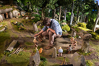 Early Man (2018) <br /> Set dresser working on the tribe's valley<br /> *Filmstill - Editorial Use Only*<br /> CAP/KFS<br /> Image supplied by Capital Pictures
