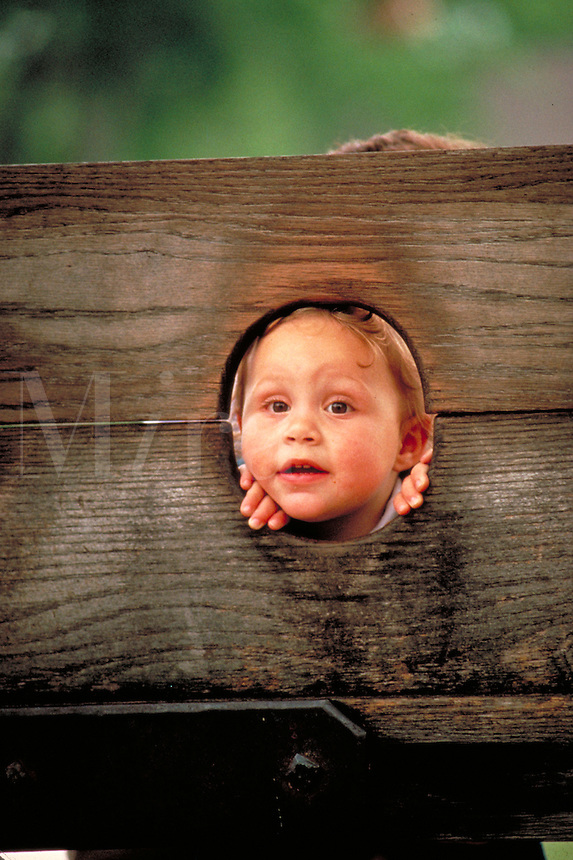 Three year old child peers through wooden stocks placed next to the Court house in Colonial Williamsburg. Williamsburg Virginia.