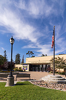 The main entrance to the lovely municipal auditorium at South Gate Park, showing the flag, lighting, mature trees, and streaks of clouds in a blue sky.