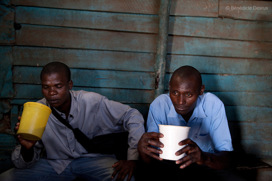 Two Kenyans men drink Busaa, a traditional fermented beer, in a busaa club at midday in a Nairobi slum on March 27, 2013. Busaa is made by crudely fermenting maize, millet, sorghum or molasses. At Kshs 35 per liter it is much cheaper than a Kshs120 half-liter bottle of commercial beer. The local brew was legalised in 2010 and since then busaa clubs have become increasingly popular. Drinking is on the rise in Kenya, especially among young people. Photo: Benedicte Desrus