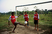 Altamira, Brazil. Football; Campealta Co-operative team in Nike Arsenal football shirts against the rest, barefoot.