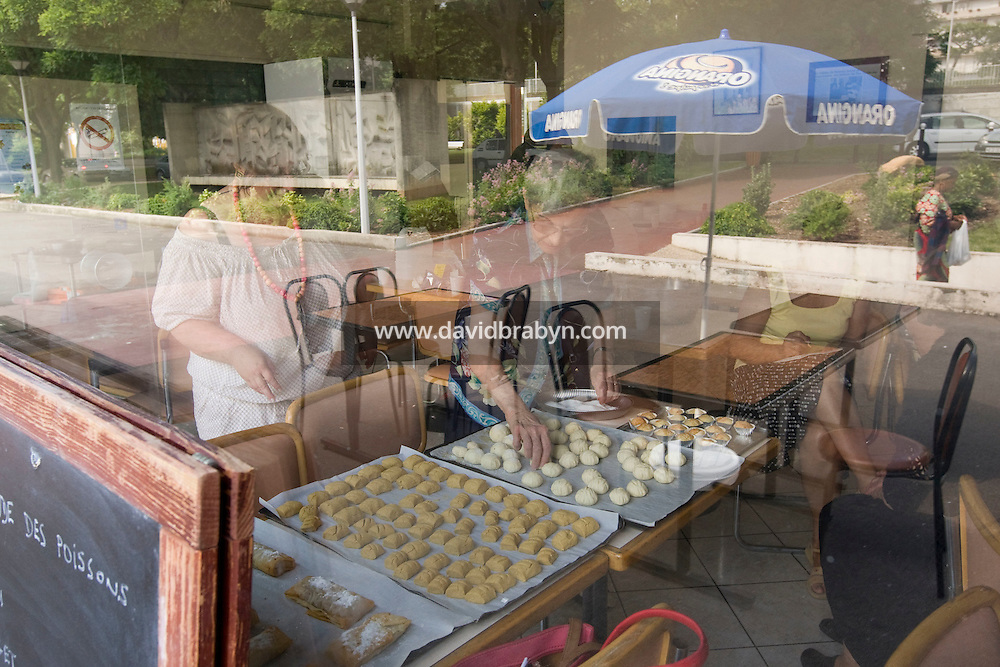 Mary Levy (C) lays out freshly cooked pastries during an Oriental pastry workshop held by the non-profit association Batisseusses de Paix (or Women Peace Builders) that seeks to build ties between Muslim and Jewish women, in a restaurant in Creteil, outside Paris, France, 24 June 2008.