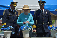 May 10, 2013  (Washington, DC)  Prince William County, VA. Police Chief Stephan Hudson (r) escorts the loved one of a fallen officer as she dedicates a flower during a ceremony at the Washington Area Law Enforcement Memorial.  (Photo by Don Baxter/Media Images International)