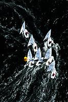 Kieler Woche:EUROPA, DEUTSCHLAND, SCHLESWIG- HOLSTEIN 22.06.2005:Kieler Woche, Segler der Laser Klasse im Gedraenge an der Wende. <br /> Der Laser ist eine 4,23 m lange, 1,37 m breite und 57 kg (Rumpf) schwere Einmann-Jolle mit einem Segel.<br /> Der Laser wurde 1970 vom Amerikaner Bruce Kirby als Einhand-Jolle entworfen. Primaere Zielsetzung war damals ein Boot f&uuml;r die Freizeit zu entwerfen, deshalb auch der urspr&uuml;ngliche Name &bdquo;Freetime&ldquo;.<br /> Seine einfache Bauweise und niedrige Anschaffungskosten f&uuml;hrten zu einer raschen Ausbreitung. Ende des Jahres 2004 gab es ca. 180.000 Boote auf der Welt!<br /> Der Laser ist eine One-Design Bootsklasse und wird von der Firma Performance Sailcraft Ltd. in England gefertigt. Weiterhin gibt es Lizenznehmer in Australien und in Chile.<br /> Das Niveau in der Laser-Klasse gilt als eines der h&ouml;chsten der olympischen Bootsklassen<br /> Luftaufnahme, Luftbild,  Luftansicht