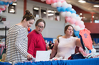 NWA Democrat-Gazette/BEN GOFF @NWABENGOFF<br /> Andrea Henson (from left), of Fayetteville, who is expecting her first child, shops for baby clothes with mother Carol Baughman of Fayetteville and mother-in-law Kim Henson of Rogers at the Sam's Club table Saturday, March 10, 2018, during the Power 105.7 Worlds Largest Baby Shower at the Jones Center in Springdale. The event sponsored by Washington Regional, with proceeds from ticket sales going to March of Dimes, included a variety of vendors, activities and seminars to help new and expecting parents provide the best care for their babies.