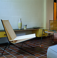 The wall-mounted cabinet and glass coffee table in the living area were designed by Jason Maclean and the pair of string chairs by Alan Gould