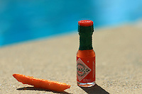 small tabasco hot sauce bottle and sweet potato fry by the poolside