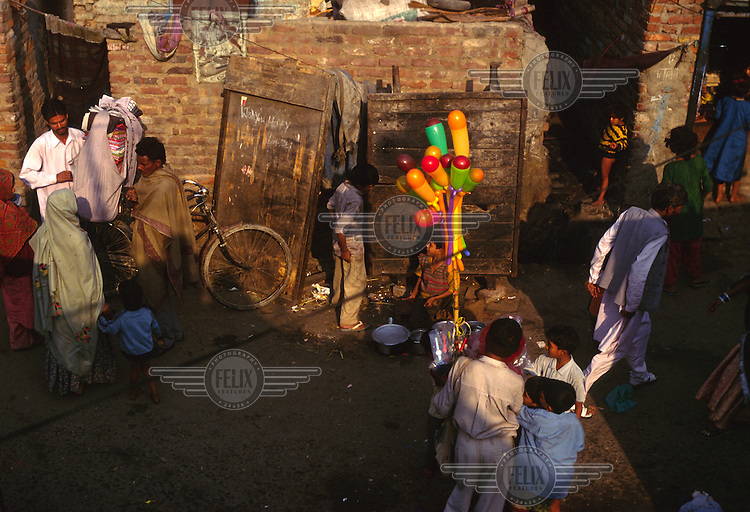 A child sells balloons while passers-by chat in a street in Shadipur Depot.