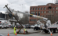 NWA Democrat-Gazette/DAVID GOTTSCHALK  Personnel with Southwestern Electric Power Company work Wednesday, March 13, 2019, to replace a class 40 utility pole in the parking lot of St. Paul's Episcopal Church in Fayetteville. The pole was hit by a garbage truck emptying a dumpster and caused an electrical outage to the church around 5:00 a.m.. SWEPCO personnel replaced the pole and a transformer bank returning power to the church by early afternoon Wednesday.