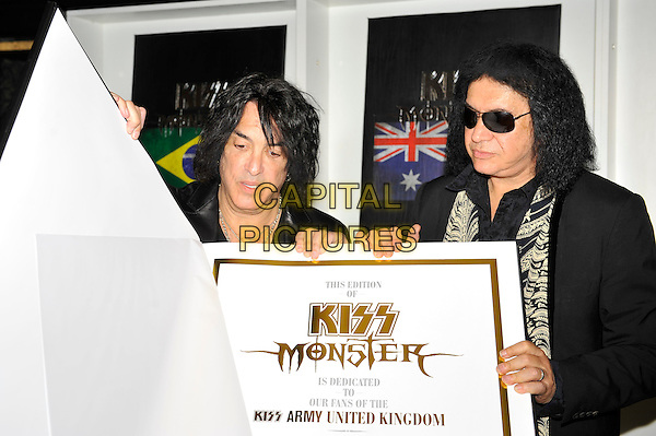 Paul Stanley and Gene Simmons.attending the 'KISS Monster' book launch, The Arts Club, London, England. .3rd July 2012.half length jacket black leather giant large oversized book sunglasses shades .CAP/MAR.© Martin Harris/Capital Pictures.