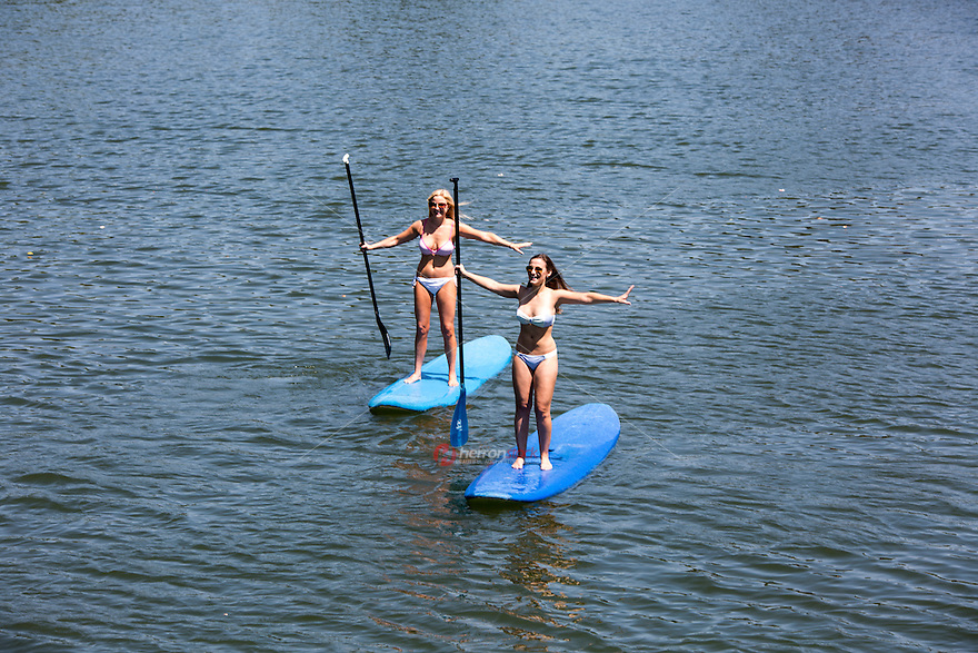Attractive fit female surfers SUP Stand Up Paddling on Lady Bird Town Lake in Austin, Texas, Active Life Concept