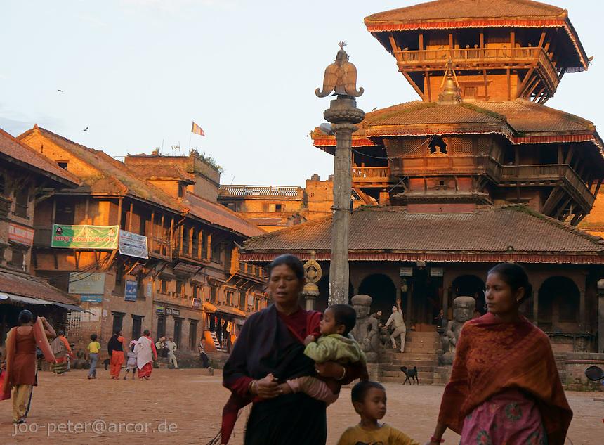 street scene on Tachapol Square  in Bhaktapur,Nepal in Bhaktapur,Nepal with woman and children, warm sunset-light