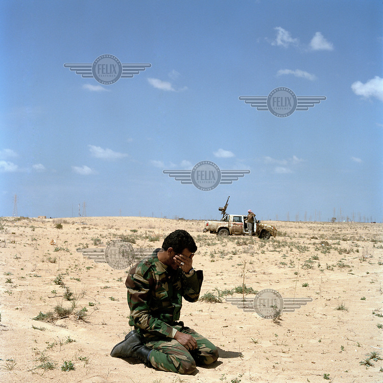 A rebel fighter pauses for afternoon prayers in the desert near Ajdabiya. On 17 February 2011 Libya saw the beginnings of a revolution against the 41 year regime of Col Muammar Gaddafi.