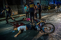 "MANILA, PHILIPPINES - OCTOBER 03: Scene of the crime police investigators gather evidence in what apeared to be an extra juducial killing of Frederick Mafe, 48, and Arjay Lumbago, 23, as their bodies lay sprawled in the middle of a street, where they were gunned down by unidentied men in a ""riding-in-tandem"" killing on October 03, 2016 in Manila, Philippines. According to locals they were shot dead by a man on the back of a bike riden by another man,  as they were driving alongside them. <br /> Photo Daniel Berehulak for The New York Times"