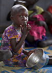 A girl relishes the last of her food as she eats in an emergency feeding program for malnourished children at the Loreto Girls School in Rumbek, South Sudan. The school, run by the Institute for the Blessed Virgin Mary--the Loreto Sisters--of Ireland, has opened its compound to hundreds of nearby villagers facing hunger because of ongoing conflict and climate change.