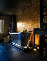 The theatrical effect of the shiny steel bath tub is enhanced by the gilt paint-effect on the bathrooom wall