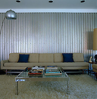 A beige 1960s sofa stands against a corrugated metal wall