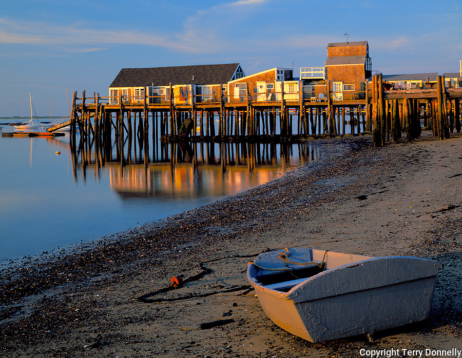 Cape Cod National Seashore, MA<br /> Dinghy stranded at low tide with Captain Jack's Wharf in the distance in Provincetown Harbor