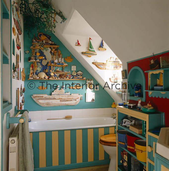 A small attic bathroom has been decorated in a nautical theme with every available wall crowded with objects
