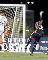 New England Revolution midfielder Saer Sene (39) takes a shot. In a Major League Soccer (MLS) match, the New England Revolution (blue) defeated D.C. United (white), 2-1, at Gillette Stadium on September 21, 2013.