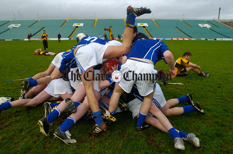 The lads from St. Flannan's pile up in celebration as Clonlara's Oisin O Dalaigh of the losing side,  Ardscoil Ris comes to terms with the loss, following the Dean Ryan Cup Hurling Final at the Gaelic Grounds in Limerick. Photograph by John Kelly.