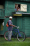 BELIZE - SEPTEMBER 11, 2007: A woman with two children talks out of her window with a man holding a bicycle along the Western Highway between Belmopan and San Ignacio on September 11, 2007 in Belize.  (PHOTOGRAPH BY MICHAEL NAGLE)