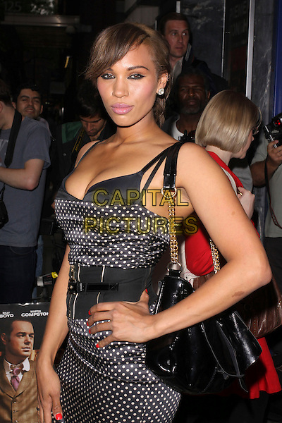 JAVINE HYLTON .Attending UK Film Premiere of 'Pimp' at Odeon Covent Garden, London, England, May 19th 2010. .arrivals half length black and white polka dot dress hand on hip bra bustier chain strap bag waist belt red nails nail varnish polish .CAP/AH.©Adam Houghton/Capital Pictures.