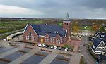 Foto: VidiPhoto<br /> <br /> LUNTEREN &ndash; In Lunteren op de Veluwe wordt dinsdag volop geklust in de gloednieuwe kerk van de Hersteld Hervormde gemeente van Lunteren. Het imposante godshuis heeft om en nabij de 8 miljoen euro gekost. Bijzonder is dat een deel van de bouwkosten geleend is bij kerkgangers. Ondanks zijn klassieke uiterlijk, is het gebouw van aller moderne gemakken voorzien. De kerkzaal heeft een kleine 1200 zitplaatsen en er zijn negen bijzalen. De huidige kerk is de helft kleiner, waardoor er zondags vier diensten gehouden moeten worden. Dat is vanaf half december niet meer nodig. Ondanks de ontkerkelijking in ons land, groeien de reformatorische kerken nog steeds en worden er ook nog nieuwe kerken gerealiseerd. In het buurdorp Barneveld zijn een paar jaar geleden twee nieuwe kerken naast elkaar gebouwd met ruim 2000 zitplaatsen. De bouw van een kerk met een klassiek uiterlijk, inclusief kerktoren, is echter zeer uitzonderlijk. Het nieuwe orgel kost 800.000 euro en wordt pas in 2019 opgeleverd. De parkeerplaats bij de kerk is door eigen gemeenteleden aangelegd, waarmee 100.000 euro is bespaard. Architect van de kerk is Architectenbureau Born BV en bouwer Bouwbedrijf Nap. De kerk wordt 16 december officieel in gebruik genomen.