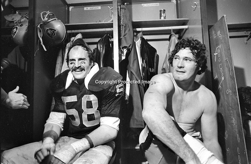 Oakland Raiders Monte Johnson and Phil Villapiano in the locker room after 1976 playoff game against the Pittlsburg Steelers. (photo 1976 by Ron Riesterer)