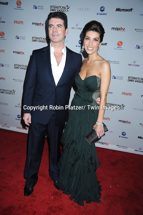Simon Cowell and fiancee Mezhgan Hussainy posing for photographers at The 38th Annual International Emmy Awards on November 22, 2010 at The New York Hilton Hotel.