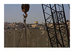 The golden Dome of the Rock Islamic Shrine in Jerusalem's Old City is seen on the horizon behind a section of Israel's controversial 8-meter-high (26 feet) security barrier that is still under construction December 30, 2003, in the Palestinian neighborhood of Abu Dis in the West Bank. Photo by Quique Kierszenbaum