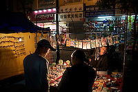 People browse a vendors goods for sale at a street market in Shaoxing, Zhejiang, China.