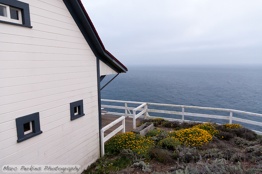 """The """"barn"""" at Point Sur Light Station.  The light station was far enough away from inhabited areas that it had a full compliment of buildings, allowing it to be self-sustaining.  This barn is one of those buildings, which has gorgeous blooming plants around it and a great view of the ocean."""