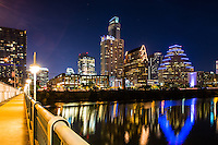 This is a view of the City of Austin skyline at night fron the first street pedestrian bridge over Ladybird Lake.