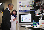 United States President Barack Obama (L) listens to Chief of the Biodefense Research Section Nancy Sullivan as he tours the Vaccine Research Center at the National Institutes of Health December 2, 2014 in Bethesda, Maryland. Obama visited the facility to discuss the ongoing fight against Ebola. <br /> Credit: Alex Wong / Pool via CNP