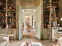A view through a pair of open double doors from a sitting room to a dining room decorated in turquoise blue. Books and other objects are displayed on shelving either side of the double doors.