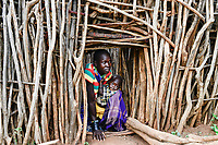 UGANDA, Karamoja, Kaabong, Karamojong tribe, Lochom village, Primina Sunday Nalamaba, 22 years, with her baby at entrance of the stick fenced village to protect the home from hostile tribes and cattle raider