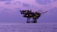 An off-shore oil rig at sunrise.