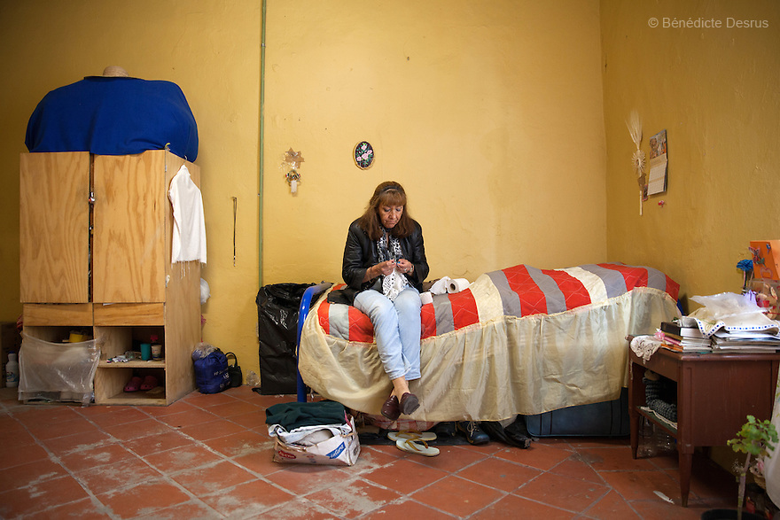 Portrait of Laeticia, a resident of Casa Xochiquetzal, in her bedroom at the shelter in Mexico City, Mexico on May 28, 2013. At the age of 8, Leticia watched as her mother said goodbye from the back of a trailer. She never saw her again. Originally from Chihuahua, Mexico, Leticia began working at nightclubs and eventually married. She didn't walk out on her husband when he hit her—he made good money—but she did leave when he brought other women into their house. She abandoned everything, including her children, and has tried twice to commit suicide. At Casa Xochiquetzal, she practices yoga daily and tries to be a peacemaker and a good housemate; however, her sweet expression can quickly turn to anger. She stays active by knitting, embroidering, and reading the Bible. Casa Xochiquetzal is a shelter for elderly sex workers in Mexico City. It gives the women refuge, food, health services, a space to learn about their human rights and courses to help them rediscover their self-confidence and deal with traumatic aspects of their lives. Casa Xochiquetzal provides a space to age with dignity for a group of vulnerable women who are often invisible to society at large. It is the only such shelter existing in Latin America. Photo by Bénédicte Desrus
