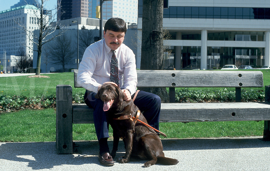 Blind man with trained dog.