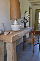 A table lamp on a rustic style table in guest room in Le Pressoir, a 14th century mill converted into holiday lets in the grounds of the Chateau de la Bourlie in the Dordogne